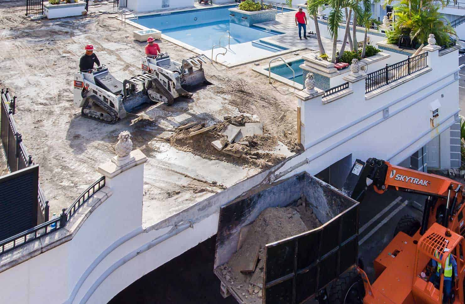 Workers Removing dirt and debris off of rooftop pool deck